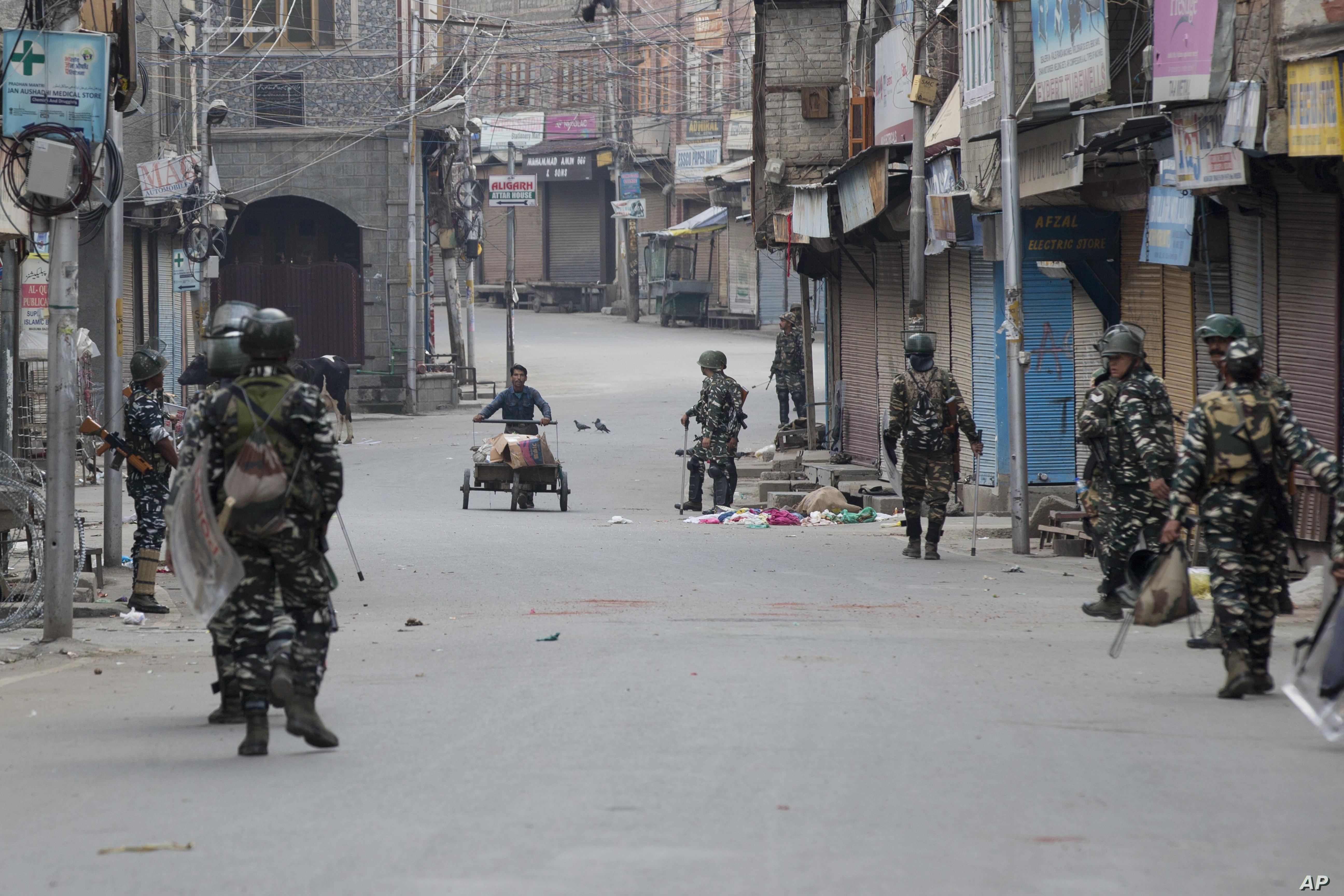 A Kashmiri municipal worker pushes a trash cart as Indian paramilitary soldiers patrol during curfew in Srinagar, India-controlled Kashmir, Aug. 6, 2019.