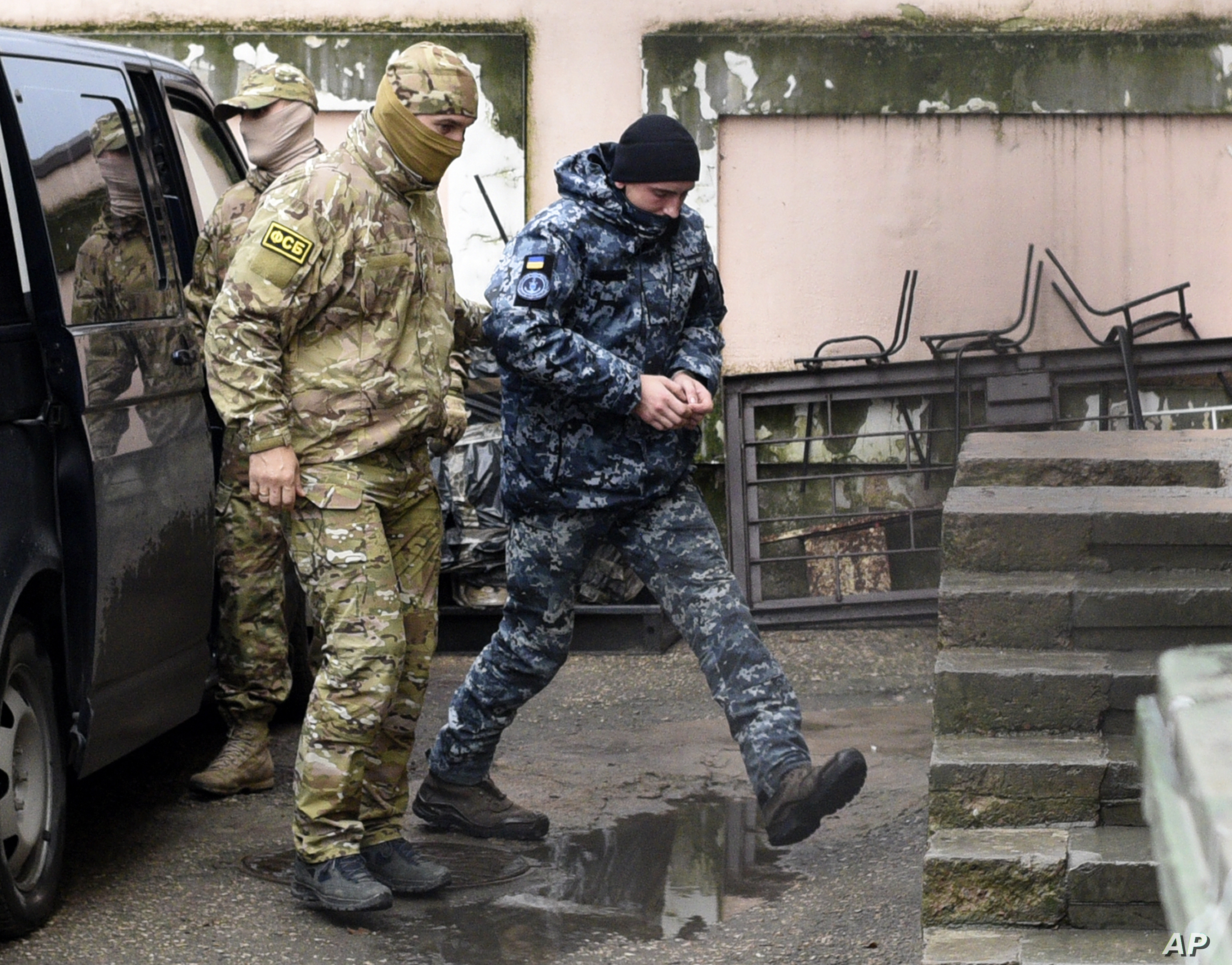A Ukrainian sailor, right, is escorted by Russian intelligence agency FSB officer to a court room in Simferopol, Crimea, Tuesday, Nov. 27, 2018. A Crimean court has ordered one of the Ukrainian seamen captured by Russia at the weekend held in…