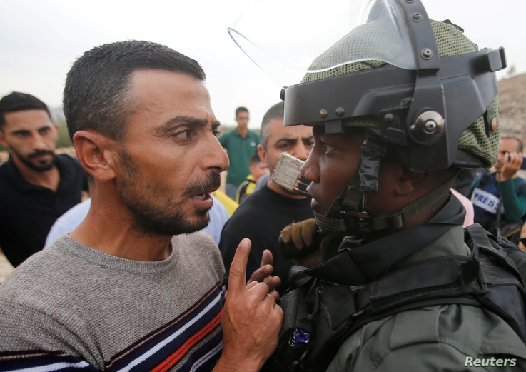 A Palestinian demonstrator argues with an Israeli border policeman during a protest against Jewish settlements near Hebron, in…