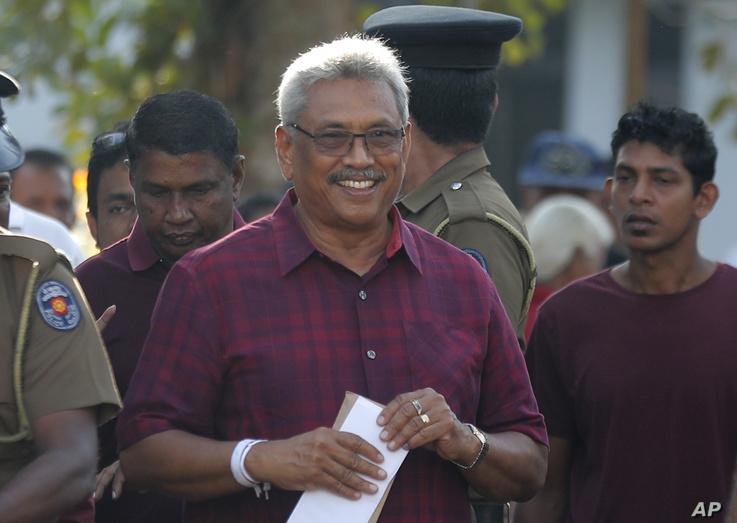 Sri Lanka's former Defense Secretary and presidential candidate Gotabaya Rajapaksa, center, leaves a polling station after…