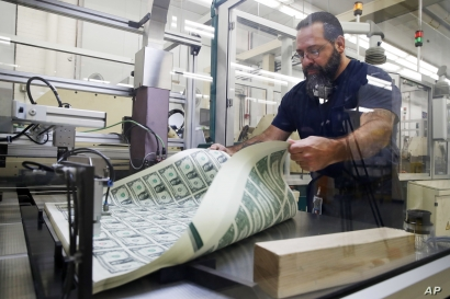 FILE - A worker aerates printed sheets of dollar bills at the Bureau of Engraving and Printing in Washington, Nov. 15, 2017.